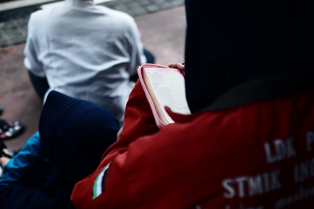 Akhwat dari organisasi kampus khusyuk membaca Al Quran sembari menunggu aksi